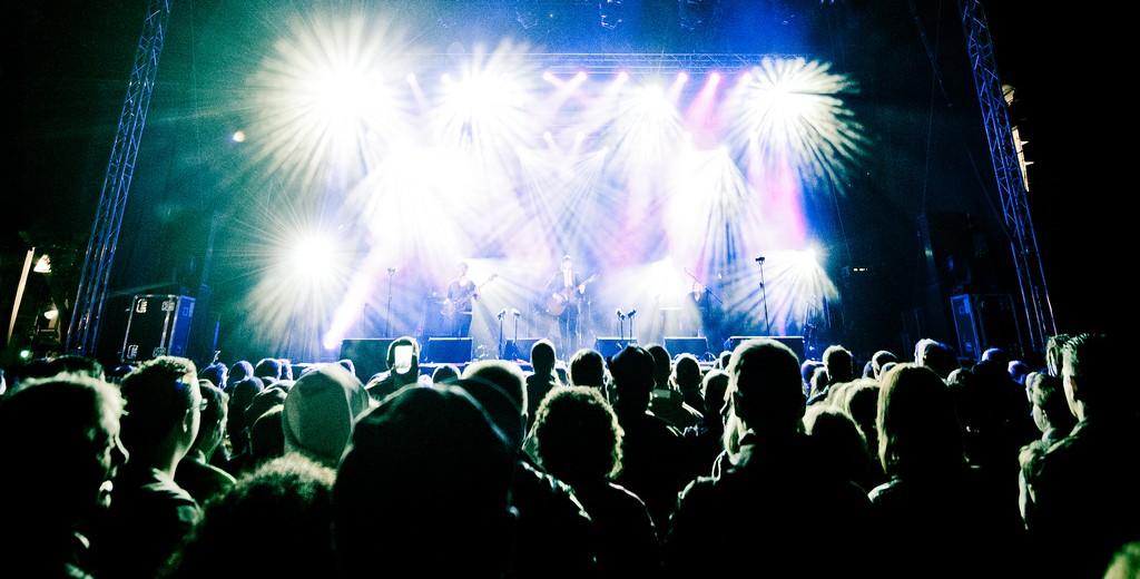 Publico de Pie viendo hacia un escenario lleno de luces