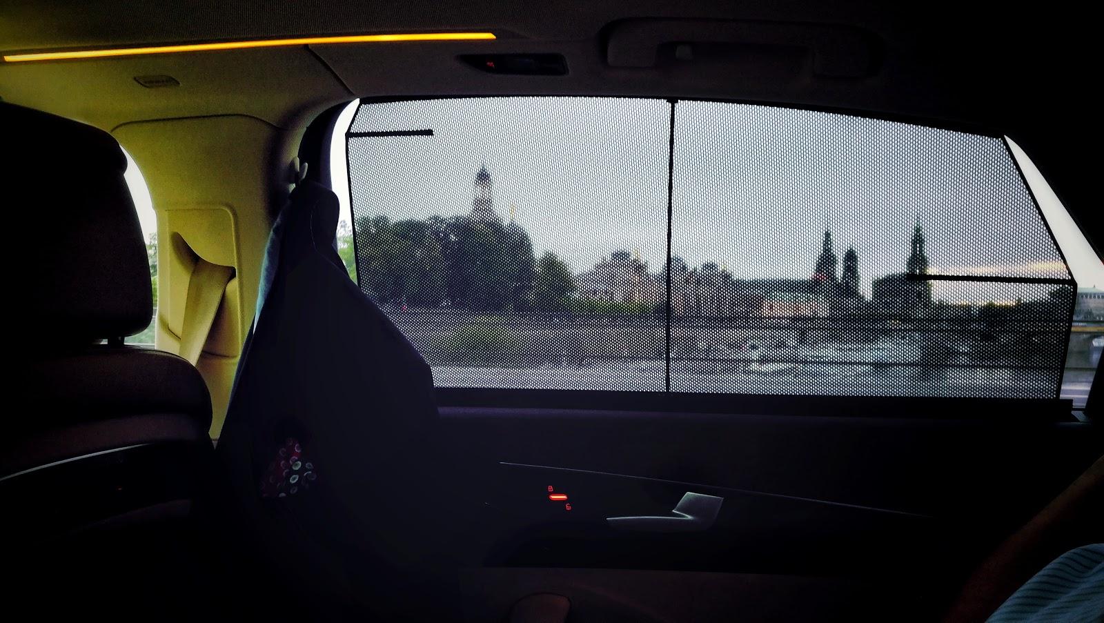 Ein Jacket hängt am Fenster einer Audi Limousine man sieht den beleuchteten Innenraum
