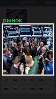 стоят люди как на рынке перед мониторами, биржа работает
