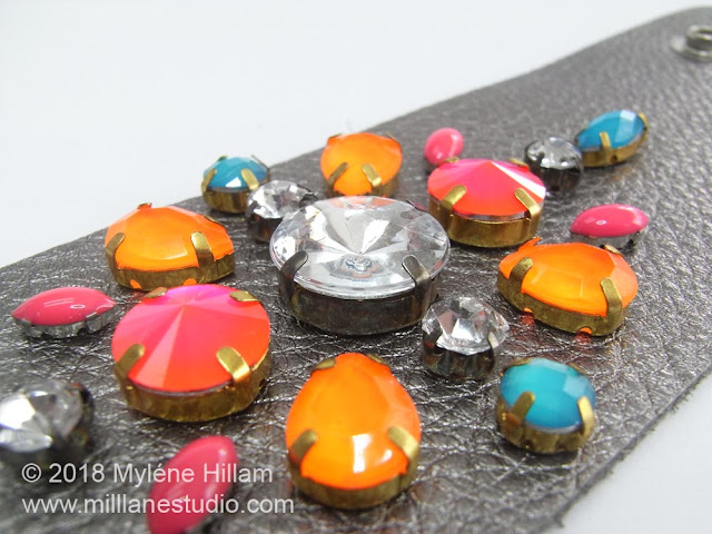 Close up of the neon bright crystals on a flat metallic leather cuff.