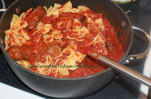 this is a big pan of bow tie pasta with meat in it