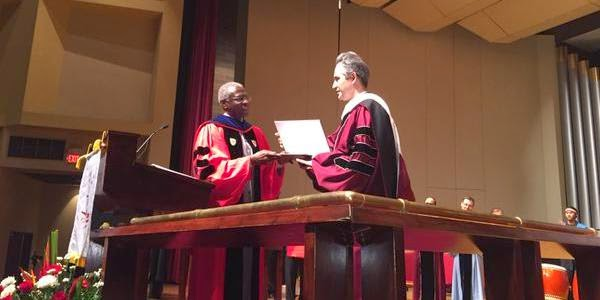 On behalf of Fethullah Gulen, Dr. Aslandogan of the AfSV receives the Gandhi King Ikeda Peace Award from Dean Carter.
