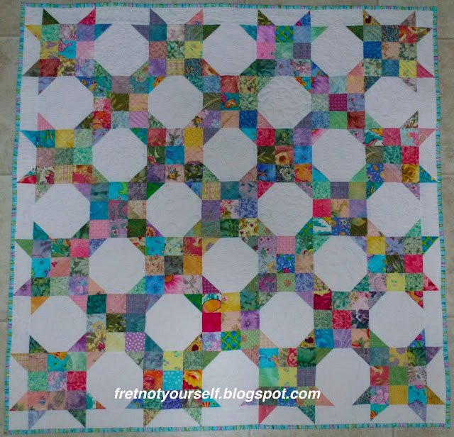 Cheerful pastel and medium prints on a white background. The half width border emphasizes stars in the nine-patch snowball combination of this quilt.