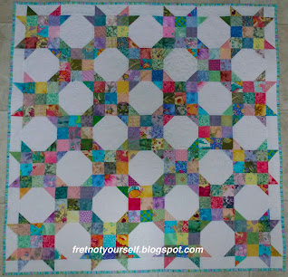 Cheerful pastel and medium prints on white. Border creates stars for nine-patch snowball quilt.