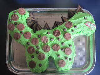 green dinosaur cake on metal tray