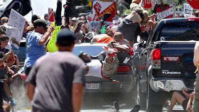 In this Aug. 12, 2017, file photo, people fly into the air as a vehicle is driven into a group of protesters demonstrating against a white nationalist rally in Charlottesville, Va.