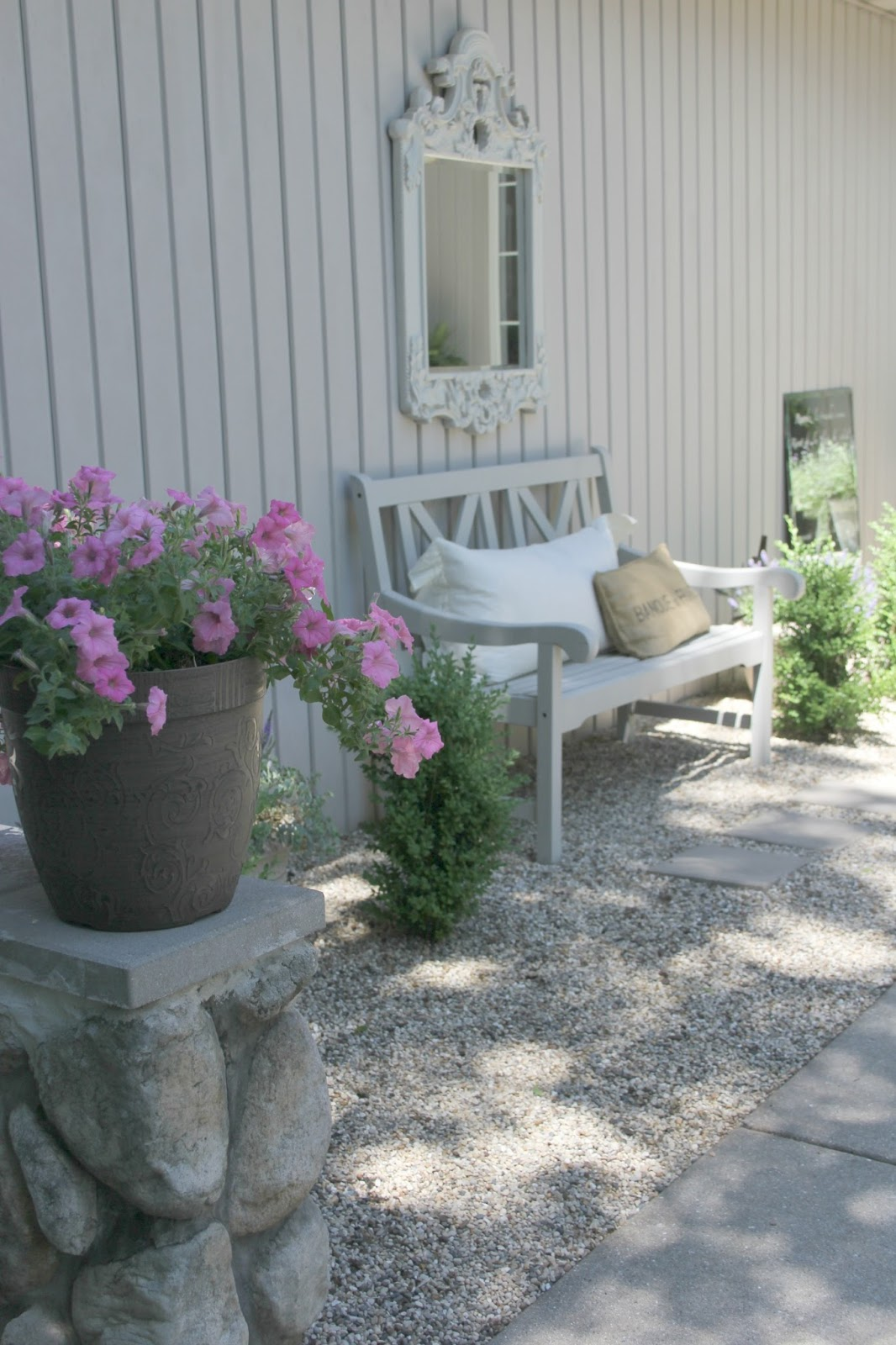 Beautiful French inspired pea gravel courtyard with bench and mirror - Hello Lovely Studio
