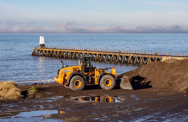 Photo of a digger removing stones from the shore by Maryport Pier