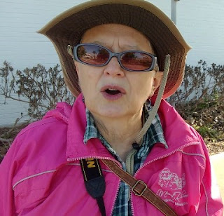 Betsy of As We Go in hat, sunglasses, pink jacket talking and looking a bit rumpled