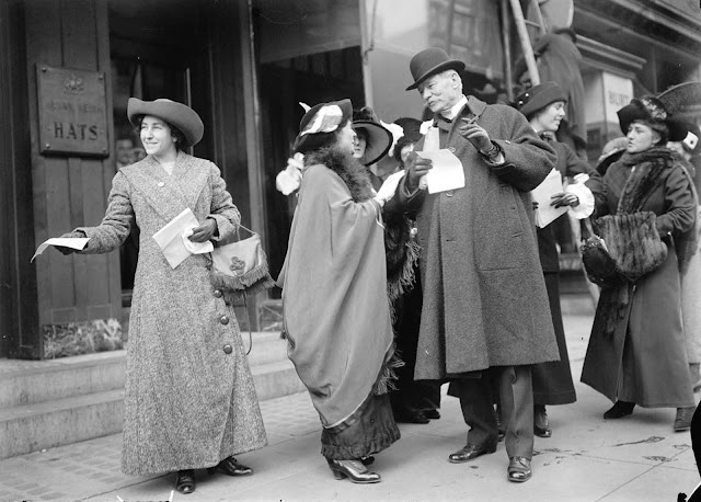Suffragists hand out flyers advertising the upcoming parade, 1913.