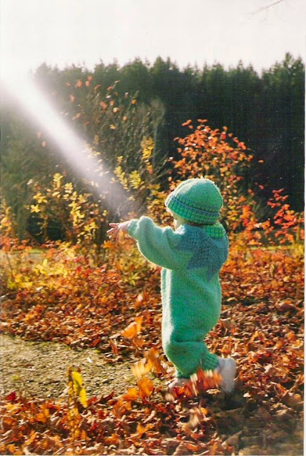 A small toddler dressed in knitted suite enjoying the sunshine on Thanksgiving day.