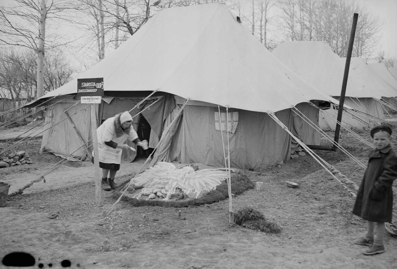A woman decorates the front yard of her tent with the Polish national eagle.