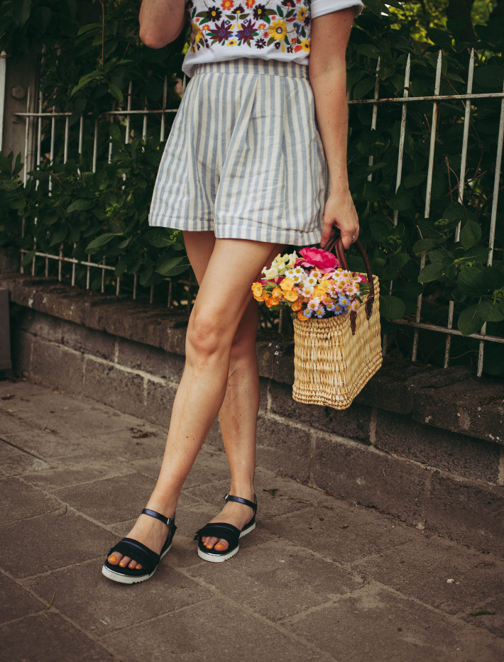Striped shorts, fringe sandals, flowers in basket