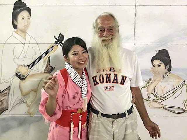 Ryukyu Mike and granddaughter in front of wall art