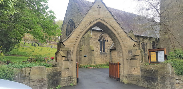 The archway of St John's Church, Holmfirth, providing a glimpse of the church and grounds.