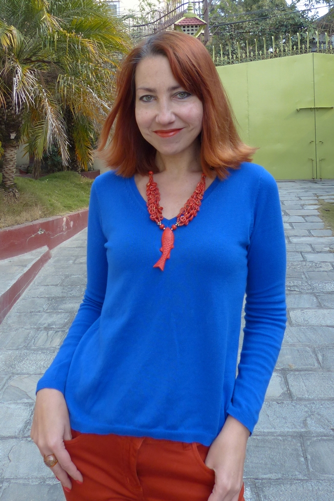 Cobalt blue v neck jumper and orange fish necklace