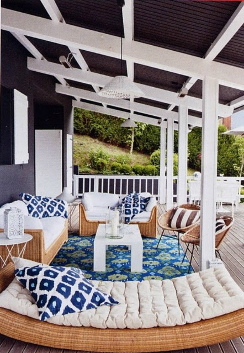 Cool blue and white coastal outdoor living room with wicker and great pillows