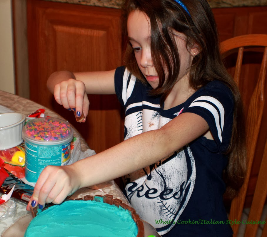 Samantha helping me make a beach scene on a spa cake with blue frosting, chocolate and sprinkles
