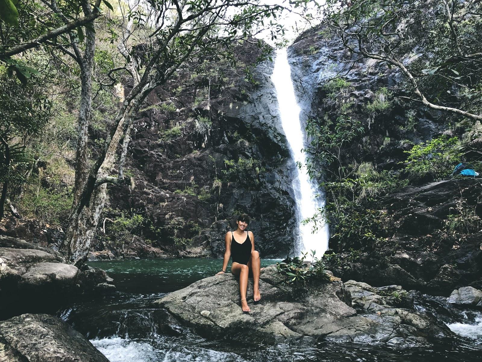 Wodospad w lesie deszczowym niedaleko australijskiego miasteczka Cardwell. Na skale przed nim siedzi podróżniczka w stroju kąpielowym.