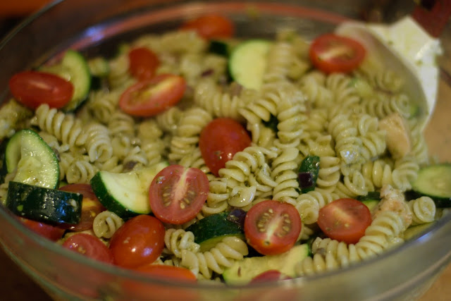 The Chicken Pesto Pasta Salad being topped with cherry tomatoes.