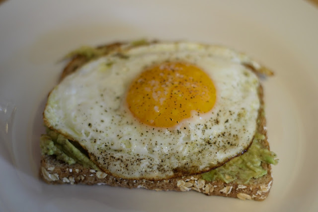A fried egg on top of the toast with avocado on it.