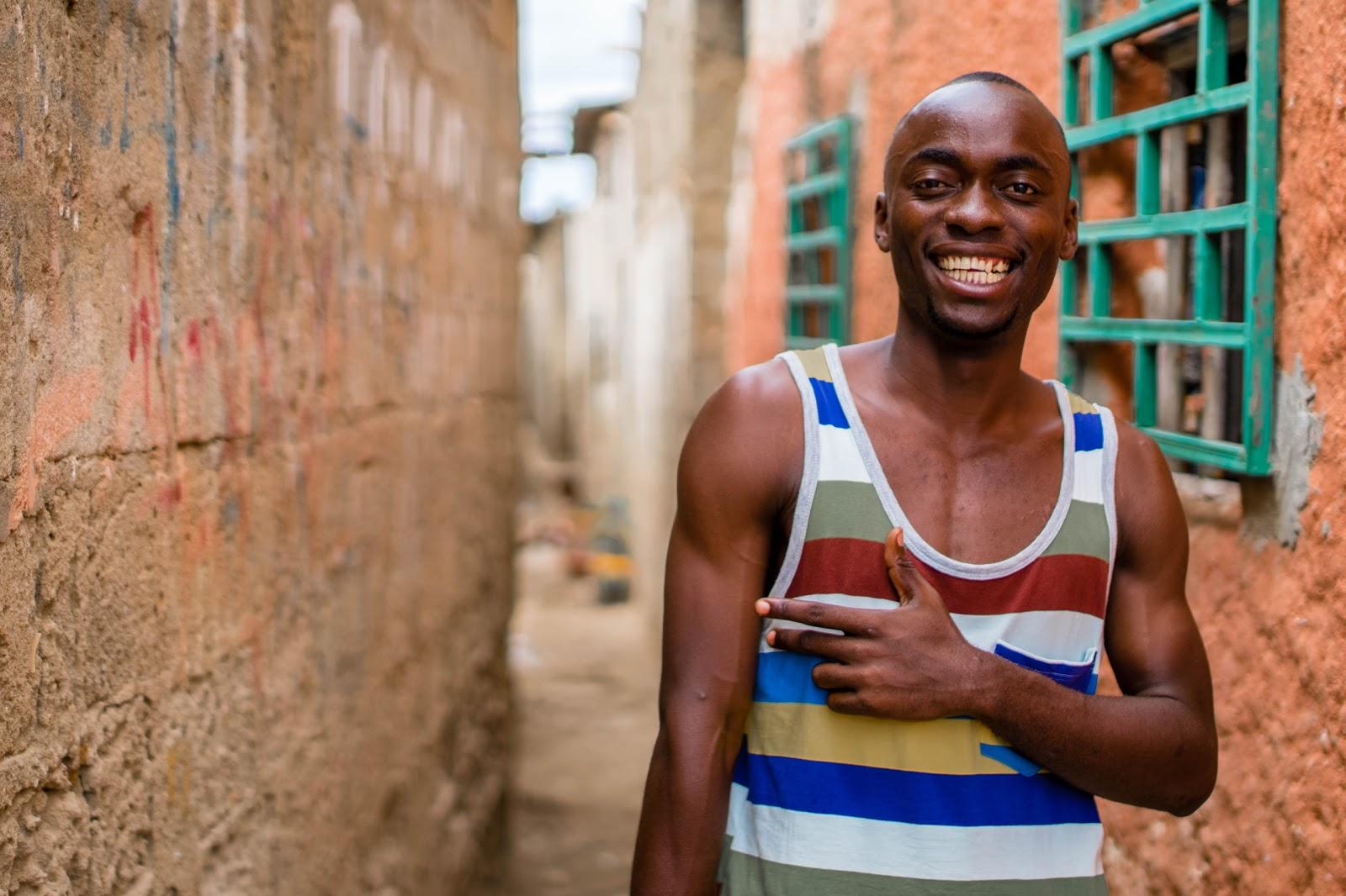 路地で黒人男性が白い歯を見せて笑っている