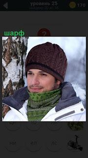 парень стоит зимой около дерева, на горле повязан шарф зеленого цвета