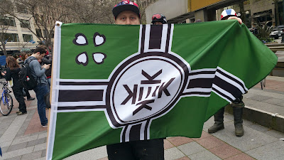 "A participant shows his ""Kekistan"" Flag in Seattle's ""May Day"" event"