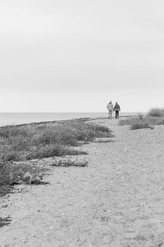Paar laeuft am Meer entlang, schwarz weiß