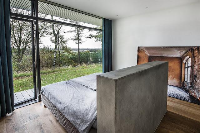 Minimalismus pur im Design, Architektur und Einrichtung – die Natur spielt hier die Hauptrolle: Beton plus Eichenholz, Schwarz-Weiß-Kontrast zu warmen Holz und viel Fensterfläche zum Ausblick