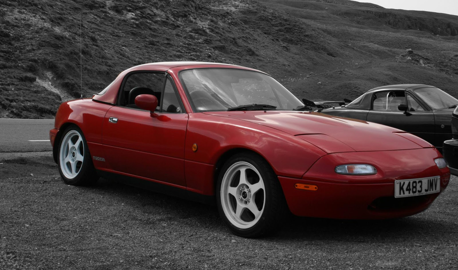 black and white photo with a colorpop of a red mx5 in the centre