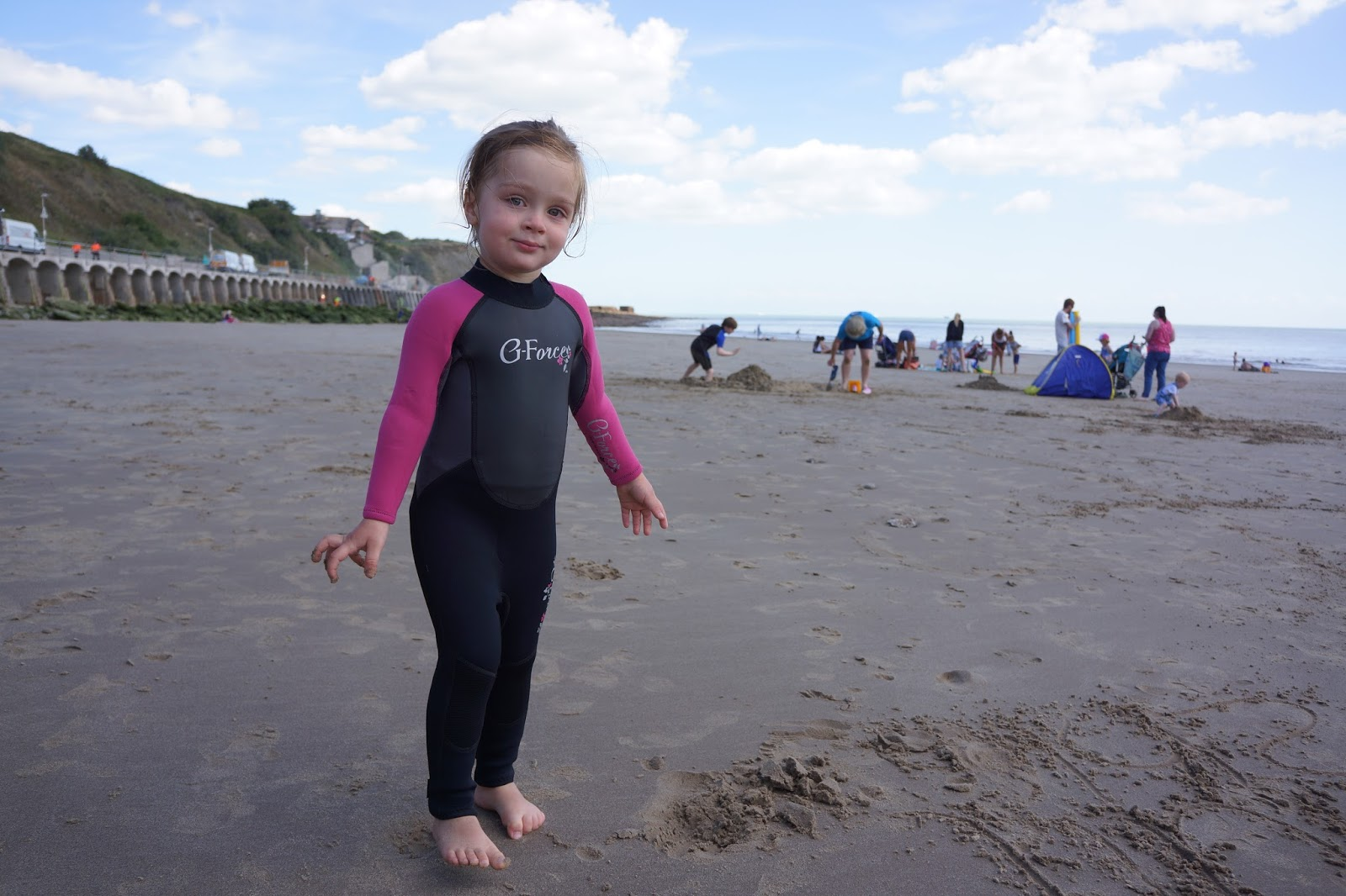 toddler wearing a wetsuit on a beach