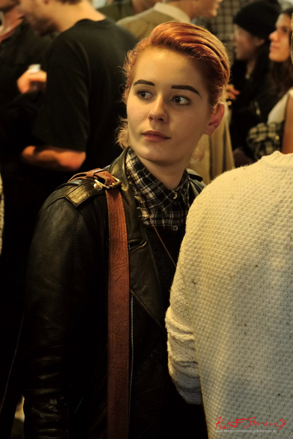 Black knit vest over check shirt under leather jacket - heavy drawn eyebrows - Women's winter style Sydney.