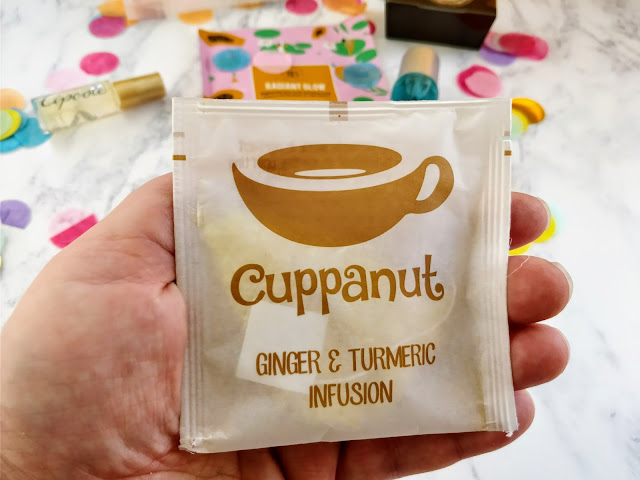 Hand holding a sachet teabag of Cuppanut Ginger and Turmeric Tea