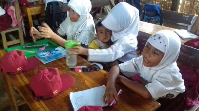 Mengharukan!! Siswi SD Menggendong Adiknya Sambil Belajar di Kelas, Kemana Orang Tuanya??