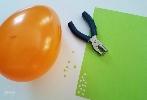 atom science experiment using  a balloon, construction paper and a hole punch