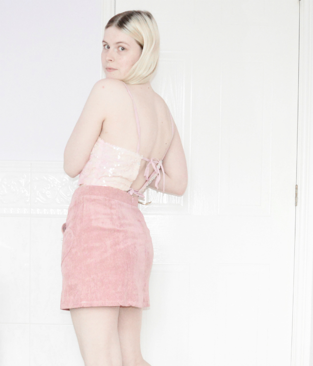 Blonde girl wearing a pink sequin crop top and a pink corduroy skirt