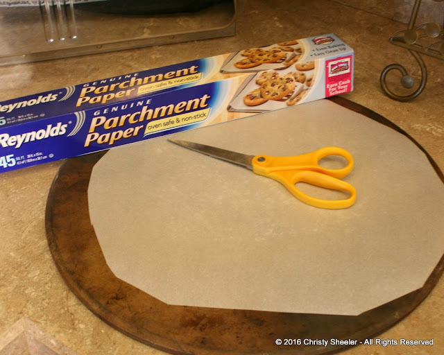 Parchment paper trimmed an inch smaller diameter than pizza stone.