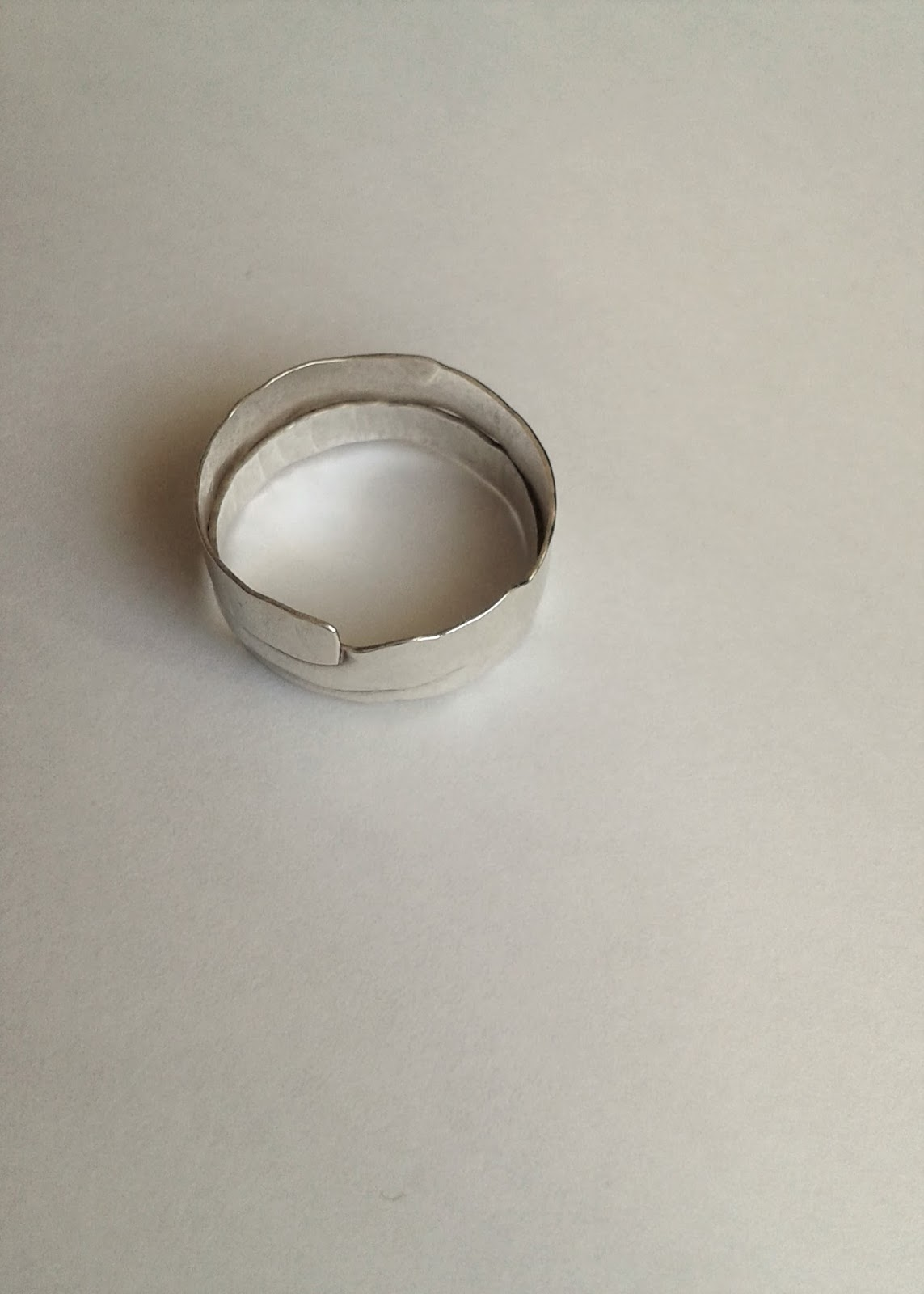 A silver ring on a plain background taken by camera phone
