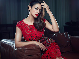 Monica Bellucci Sitting On Brown Couch