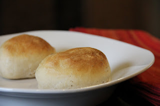 2 baked dinner rolls on a white plate