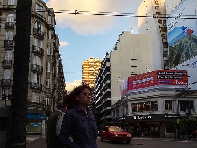 Muchacha a contraluz esperando cruzar,detrás el sol ilumina las nubes.