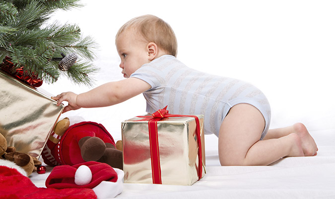 Baby reaching for gifts under Christmas tree