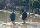 Photograph of residents of Warrengate Road escaping the Mimmshall Brook flooding of 2000. Image from the former Brookmans Park Newsletter