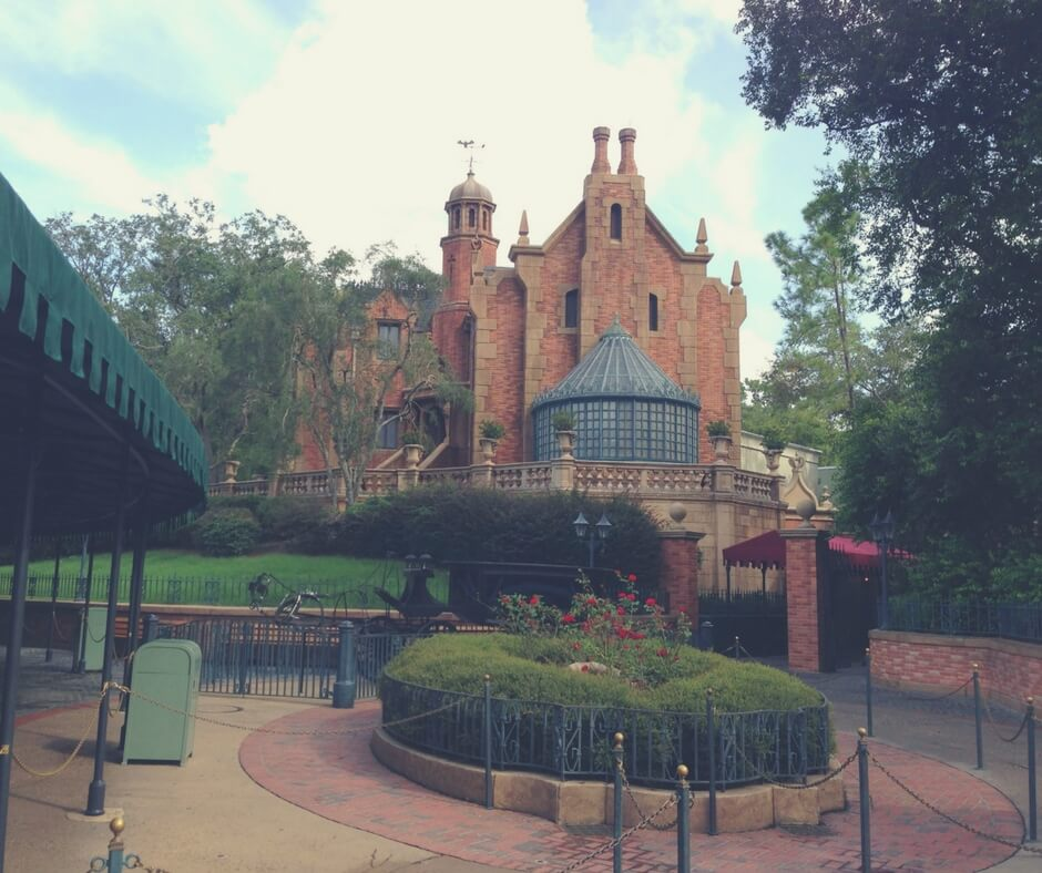 "A photo of the Haunted Mansion in Magic Kingdom. A brown bricked house stands to the right, in the background, its glass conservatory attached at the front. There is no light coming from inside. In front of the building is a rose bush, red roses growing and bright. Image for ""How to get a much-needed rest at Magic Kingdom""."
