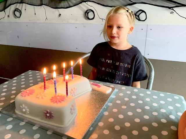 A young girl sitting behind a white iced birthday cake in the shape of a 7 getting ready to blow the candles out.