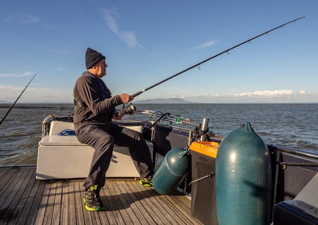 Photo of Phil fishing from Ravensdale's aft deck