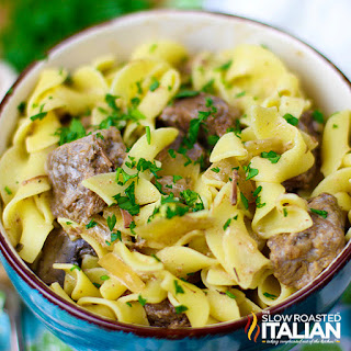 overhead photo: dish of buttery egg noodles with pieces of beef, mushrooms, and onions