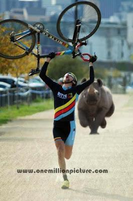 atlit berlari mengangkat sepeda dikejar badak yang mengamuk