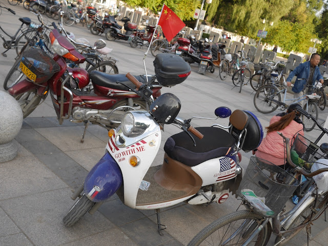 "electric scooter with an American flag and ""go with me"" design with a Chinese flag flying on it in Mudanjiang, China"